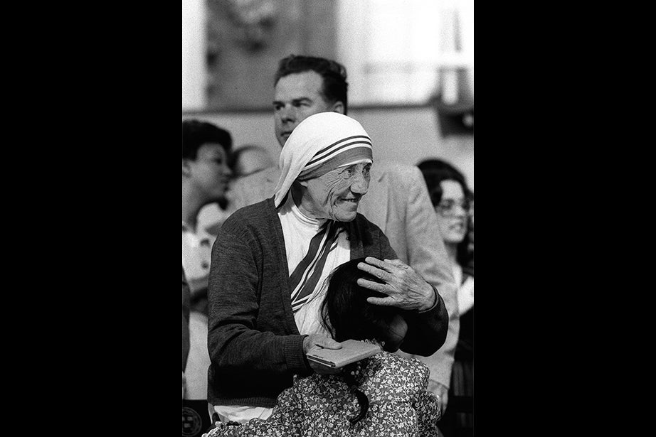 Mother Teresa hugs a child formerly from her orphanage after delivering the Class Day address in 1982, the day before she received an honorary degree at Commencement. She lived most of her life in India, where she set up schools, soup kitchens, and orphanages. She was awarded the 1979 Nobel Peace Prize. Photo by Joe Wrinn