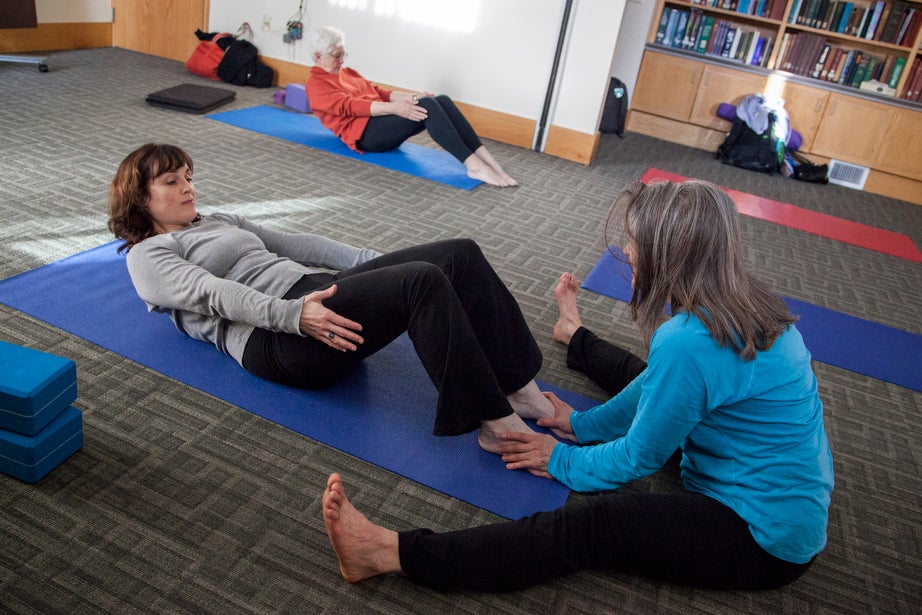Marianne Bergonzi leads Harvard employees Sarah Colgan (front) and Kathleen Fox through a yoga practice.