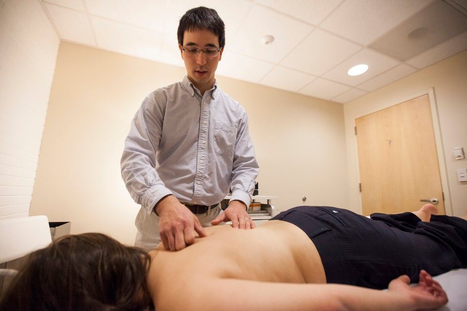 Jeffrey Matrician feels for tensions within the body after acupuncture.