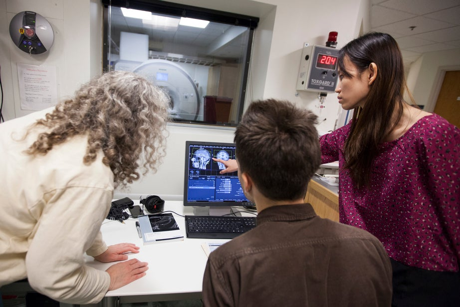 Sara Lazar (from left), Thomas Calahan, and Noel Chan observe a live MRI scan.