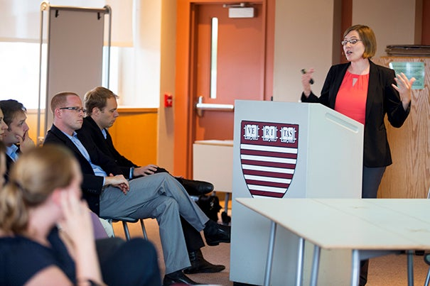 Beth Schueler (at podium), a doctoral student at the Harvard Graduate School of Education, and assistant professor of public policy Joshua Goodman (seated, wearing glasses) presented their research on the turnaround efforts of the Lawrence, Mass., school system.