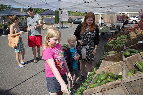 Belmont resident Cammie Wynn and her children admire the vegetables on display by E.L. Silvia Farms at the Harvard Allston Farmers' Market.