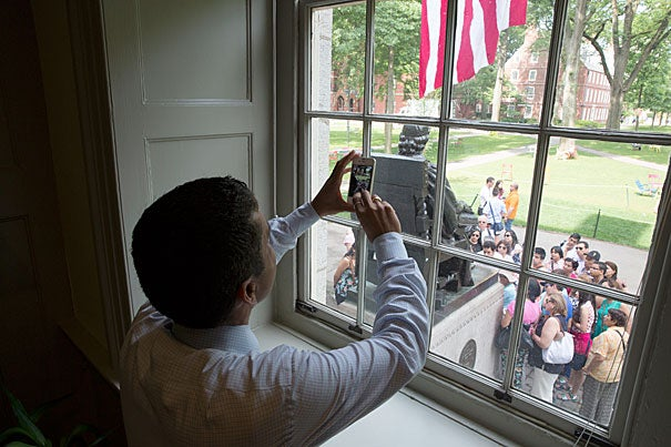 """I can't help but remember that 43 years ago this month, my family immigrated to the United States,"" said Rakesh Khurana, Harvard College's new dean (photo 1). ""Looking outside my window and seeing the flag and the John Harvard Statue, I just feel incredible gratitude to my parents, who had the courage to come to this nation."" Khurana greeted guests outside his office (photo 2), while inside he read cards from well-wishers, complete with orchids (photo 3)."