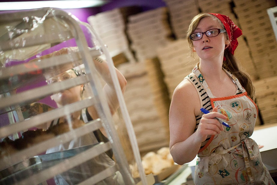 Production manager Kristen Rummel counts and boxes doughnuts intended for afternoon's farmers markets.