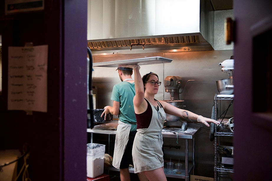Sarah Willis strikes an artful balance carrying doughnuts to the walk-in fridge to chill.