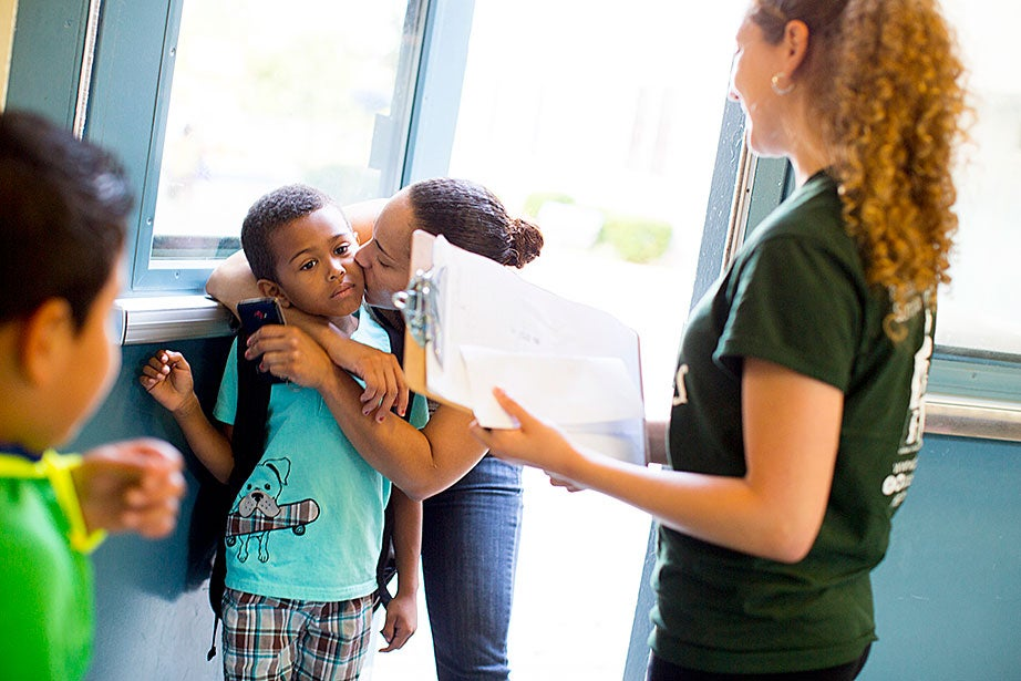Halie Olson looks on as Jayden Melo, 7, gets a goodbye kiss from his mother, Carmen, on the first day of summer school at James F. Condon Elementary in South Boston.