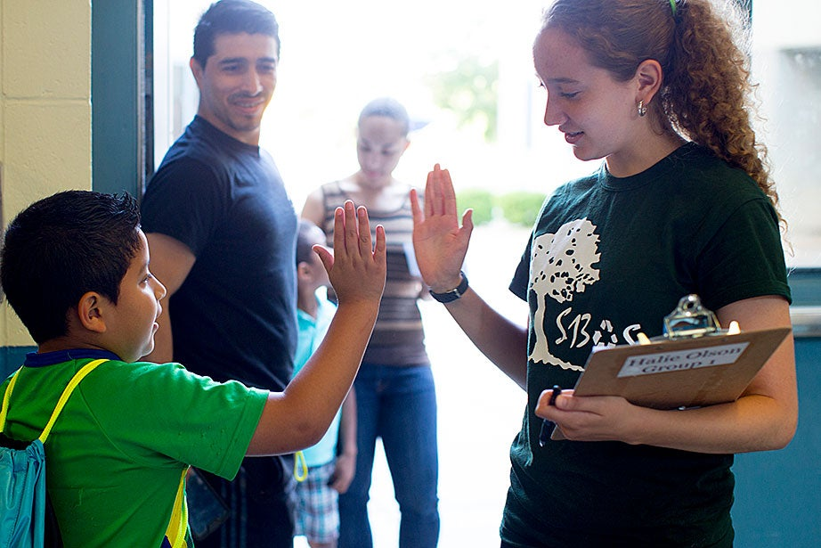 Giovanni Ortiz watches as his son, Javier, high-fives senior counselor Halie Olson '17 on the first day of camp.