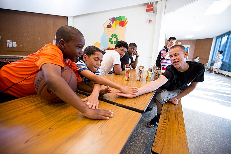 Adonis Boyce (left) and Andy Nova are happy to see Cameryn Crowley, a junior counselor this year. The campers, ranging in age from 6 to 13, all meet in the cafeteria for breakfast each morning.