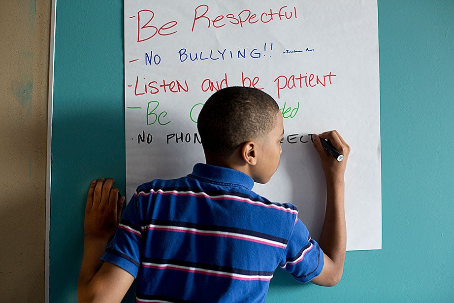 Jonathan Pierre, 12, lists the rules his class has decided collaboratively to follow. Students come from one of three public housing developments in South Boston: Old Colony, Mary Ellen McCormack, and West Broadway.