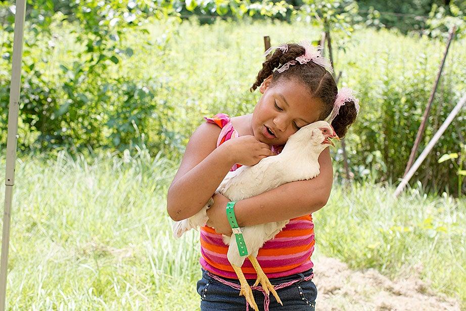 Julia Perez, 8, hugged a chicken at Farrington Farm.