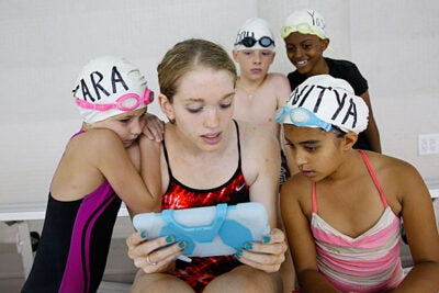 Young swimmers honed their skills at the Technique Swim Academy, one of three weekly summer athletic camps on Harvard's campus. Instructor Colleen McCormick (center, photo 1) shared a video. Harvard swim captain Kelsey Hojan-Clark '15 demonstrated a stroke (photo 2) before the young swimmers gathered in the pool (photo 3).