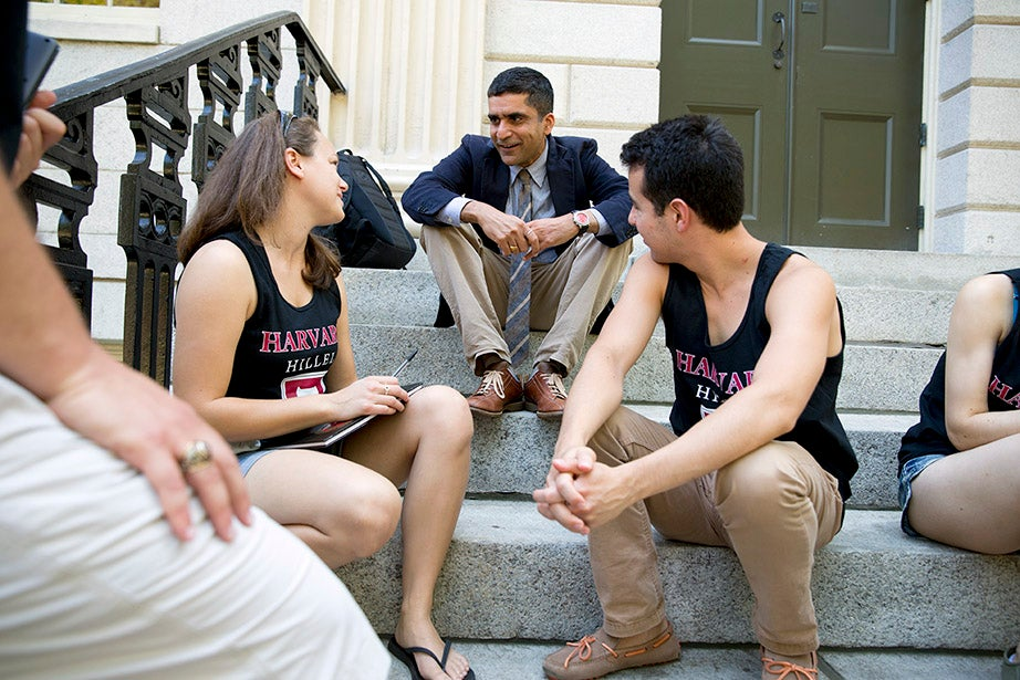 Harvard College Dean Rakesh Khurana talks with Hillel staffer Paige LaMarche (left) and Sam Fisher '15 on the steps of University Hall as freshmen move into the dormitories. Rose Lincoln/Harvard Staff Photographer