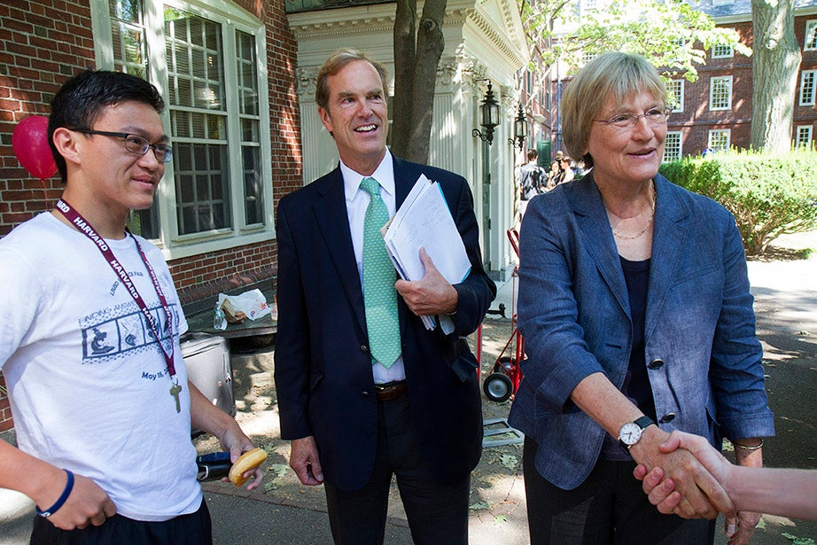 Jesse Zhang '18 watches as Freshman Dean Tom Dingman and President Drew Faust greet Zhang's classmates and their families. Jon Chase/Harvard Staff Photographer