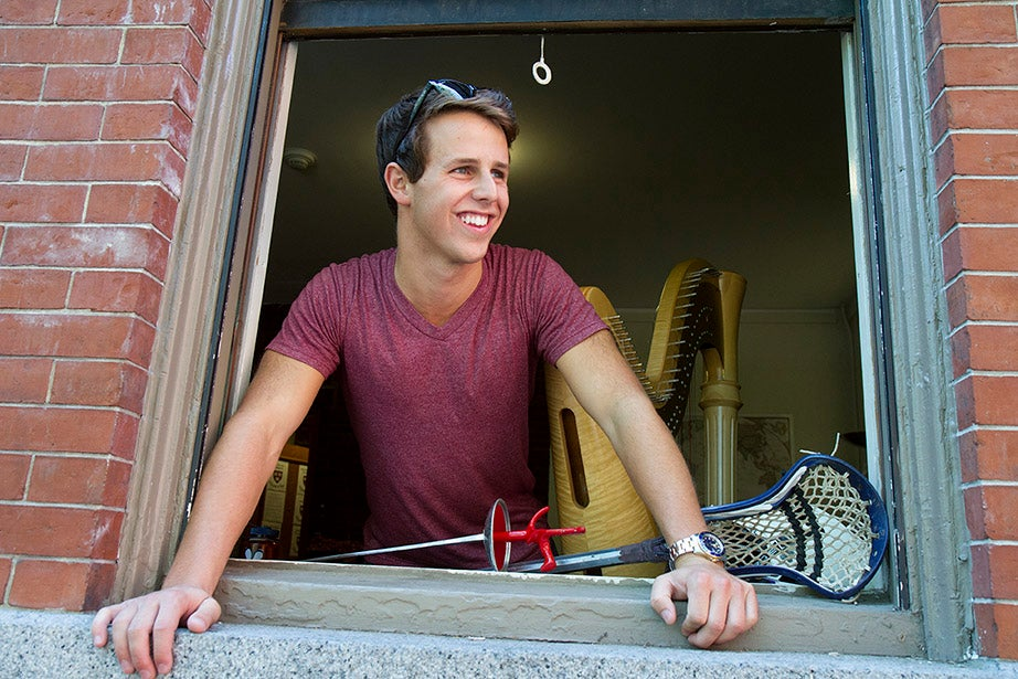 Nathaniel Horwitz '18 leans out a window of Grays Hall with his harp, fencing foil, and lacrosse stick at his side. Jon Chase/Harvard Staff Photographer