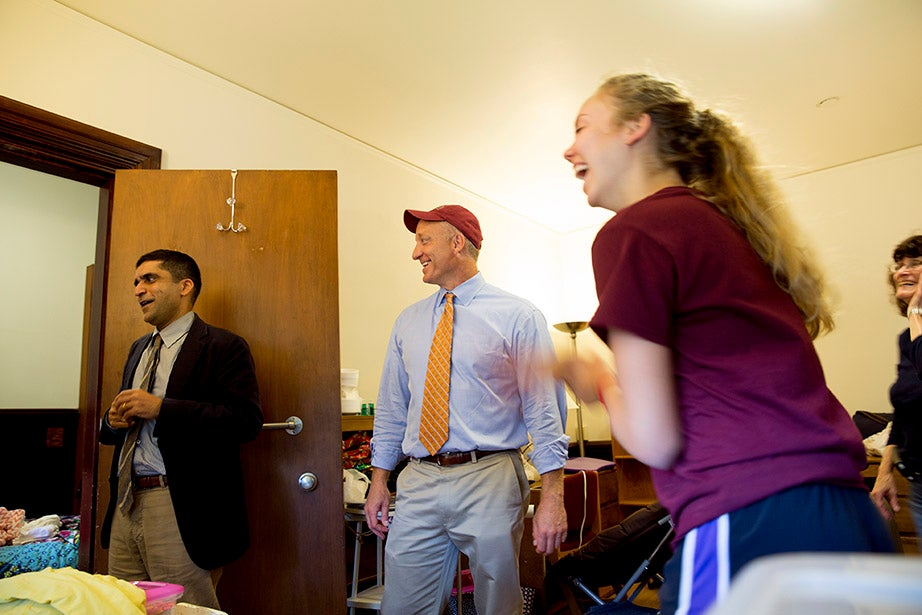 Harvard College Dean Rakesh Khurana (left) and Dean of the Faculty of Arts and Sciences Michael D. Smith greet Lauren Elson '18 in her room in Matthews Hall. Rose Lincoln/Harvard Staff Photographer
