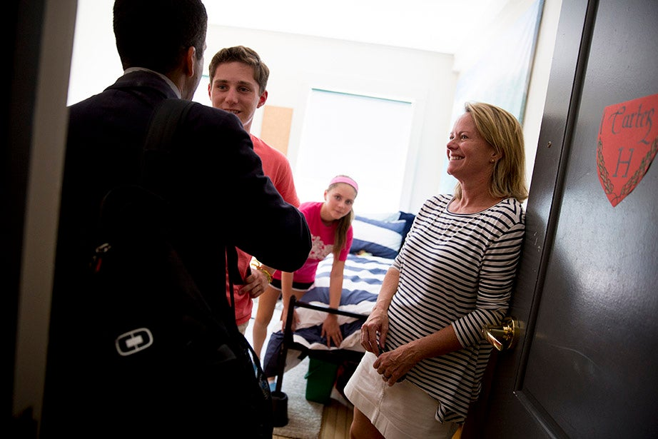 Carter Allinson '18, his sister, Brooke, and mother, Hilary, receive a welcome in Hurlbut Hall from Harvard College Dean Rakesh Khurana. Rose Lincoln/Harvard Staff Photographer