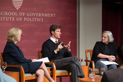 The fight to end the Ebola epidemic is not just about saving lives, it's also about heading off a potentially broader humanitarian crisis, according to a Harvard Kennedy School panel, which included (seated from left) moderator Sheila Burke, Michael VanRooyen, director of the Harvard Humanitarian Initiative, and Dyann Wirth, Richard Pearson Strong Professor of Infectious Disease at Harvard.