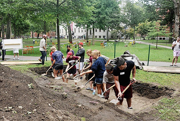 """Harvard College student Matthew DeShaw participated in the 10th annual Harvard Yard dig (photo 1), alongside Jeffrey Zhao '16 and Matthew C. Gschwend '16 (photo 2), which DeShaw said turned up """"a few pieces of coal, aggregates of rock, shards of glass, and an MBTA token"""" (photo 3)."""