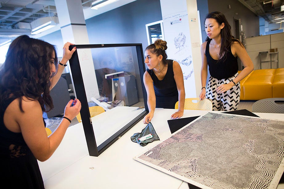 Jordyn Fahey (from left), Tatiana Fontalvo, and Charlene Lee '14 frame Scott Benner's artwork for display in a Newbury Street shop. They are part of ArtLifting, an online marketplace that showcases artwork by men and women who are homeless, disadvantaged, or disabled.