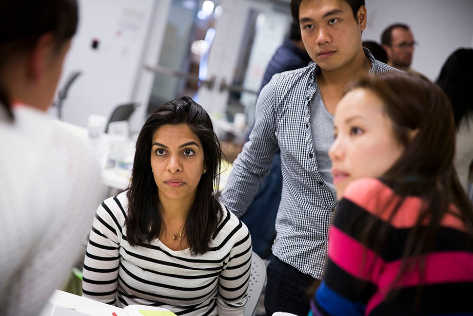 """HBS Professors Srikant Datar and Rajiv Lal teach the class """"Design Thinking and Innovation"""" in Batten Hall. Nadira Lalji and Kelvin Lam, of Harvard Business School, and Jerilyn Teo, from the Harvard Graduate School of Education, work together on an assignment."""