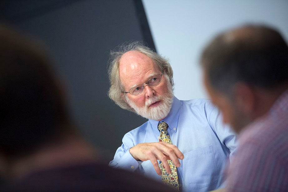 """Inside the Mineralogical and Geological Museum, James McCarthy, Alexander Agassiz Professor of Biological Oceanography, leads the discussion in his """"Environmental Crises, Climate Change, and Population Flight"""" class. Kris Snibbe/Harvard Staff Photographer"""