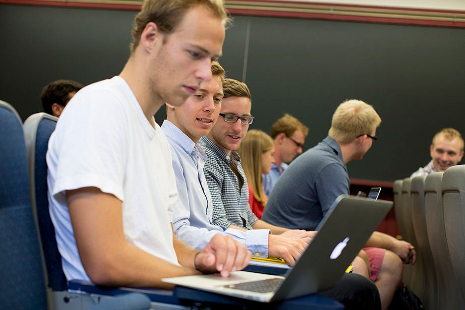 """A student checks his laptop before the start of """"Economics 1490: Growth and Crisis in the World Economy."""" Rose Lincoln/Harvard Staff Photographer"""