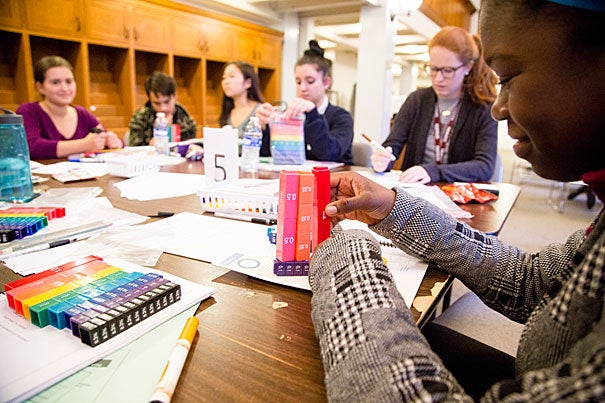 Harvard's Teaching and Learning Partnerships team trains high school students to be mentors in Boston Public School's Homework Help program. The team uses an approach developed by Harvard's SmartTALK program (photo 1). Joan Matsalia (right, photo 2), associate director of Teaching and Learning Partnerships, talks with one of the teens in training, while Renelle Lawrence (standing, photo 3), a student at the Harvard Graduate School of Education, provides guidance.