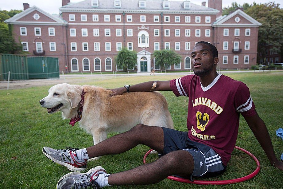 Ernest Afflu '15 relaxes at practice with Maggie, the team's canine mascot.