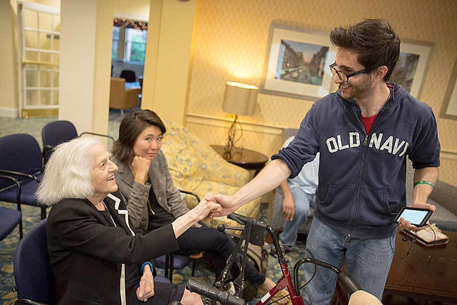 Tom Somi '14 greets Symphony Plaza Apartments resident Dee Martino.