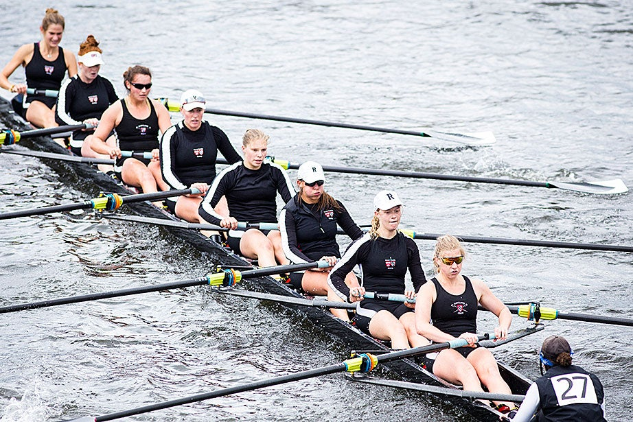 The eight rowers and the coxswain power through the Charles.