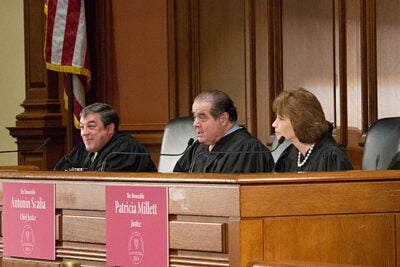 """The presiding judges for Harvard Law School's Ames Moot Court Competition were Judge Adalberto Jordan of the U.S. Court of Appeals for the 11th Circuit (from left), U.S. Supreme Court Associate Justice Antonin Scalia, and Judge Patricia Millett of the U.S. Court of Appeals for the District of Columbia Circuit. Following the students' deliberations, Scalia said, """"This is as good an argument as you are likely to hear in a court of appeals, and probably in my court."""""""