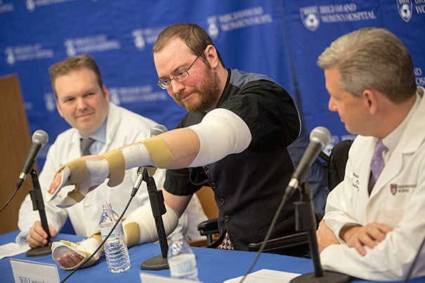 Will Lautzenheiser's moves his new left arm for reporters. Last month, Lautzenheiser received a bilateral arm transplant with the help of Simon Talbot (left), director of the Brigham's Upper Extremity Transplant Program, and Matthew Carty (right), head of the Brigham's Lower Extremity Transplant Program.