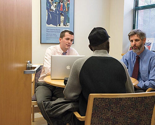 "HLS student Andrew Roach '13 (left) and Clinical Professor Daniel Nagin meet with a veteran at HLS's Veterans Legal Clinic to discuss the status of a case on appeal. The clinic's value is manifold, Nagin said, noting, ""It's a privilege to be able to advocate for someone who's sacrificed for the nation."""