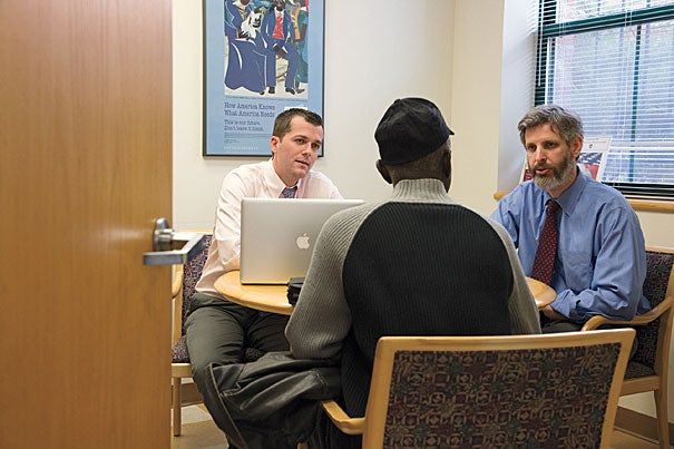 """HLS student Andrew Roach '13 (left) and Clinical Professor Daniel Nagin meet with a veteran at HLS's Veterans Legal Clinic to discuss the status of a case on appeal. The clinic's value is manifold, Nagin said, noting, """"It's a privilege to be able to advocate for someone who's sacrificed for the nation."""""""