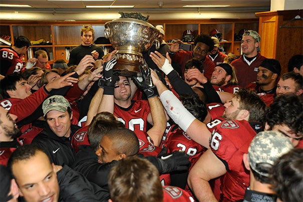 Crimson players celebrate with the Ivy League trophy following their win over Yale, 31-24. Photo by Jon Chase/Harvard Staff Photographer