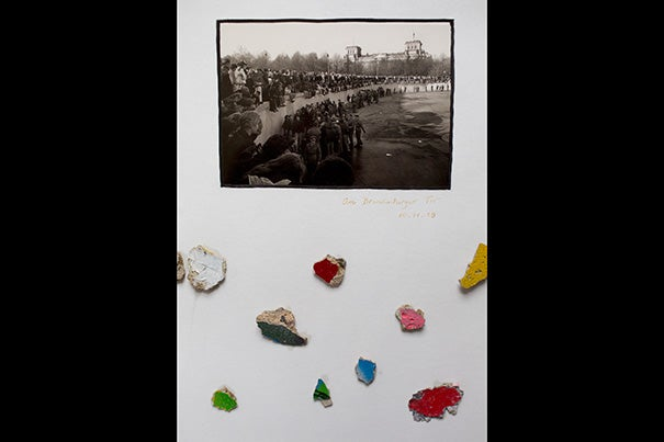 In the office of Carl H. Pforzheimer University Professor Robert Darnton hangs a framed postcard featuring a crowd dancing on the Berlin Wall. His teenaged daughter is included in the image. Darnton also added small fragments of the wall in the display.