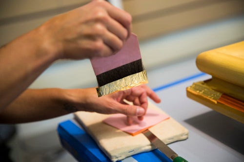 Harvard's frame conservator Allison Jackson gently gilds a new frame with leaves of 23.75-karat gold that are 1/250,000 of an inch thick. Jackson first rubs the brush called a gilders tip against her cheek. The oils from her skin help the gold stick to the brush.
