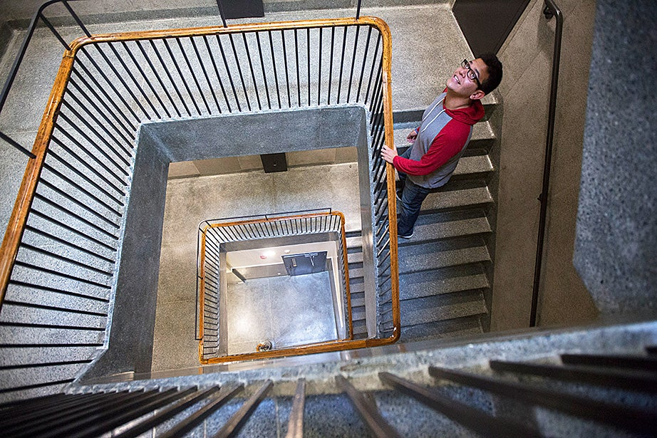 Miguel Perez-Luna climbs a historic stairwell inside McKinlock Hall. Kris Snibbe/Harvard Staff Photographer