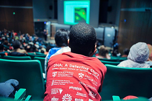 """A sea of DNA T-shirts (photo 1) filled Science Center B as hundreds gathered for Harvard's School of Engineering and Applied Sciences' annual holiday lecture. This year, Professor Howard Stone of Princeton University helped the youngsters crack the universal code and structure of DNA (photo 2), accompanied by his lecture, """"DNA: A Detective Story."""" With parents participating, Lindsey Smilack and her son, Edwin, of Cambridge fashioned DNA molecules from pipe cleaners (photo 3)."""