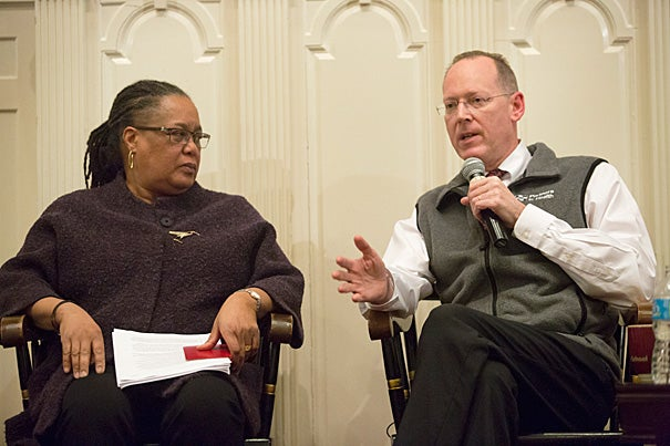 "During a Harvard-sponsored forum at First Parish in Cambridge, Professor Evelynn Hammonds (left) drew attention to the fact that epidemics ""pull the covers off"" the ways that the poor, vulnerable, and sick are perceived. Sharing her concerns was Professor Paul Farmer: ""If we had the staff, stuff, space, and systems, we could get people earlier into a place where they could get supportive care."" To date, most Americans stricken with Ebola have survived because they were ""scooped out"" of miserable conditions, he noted."