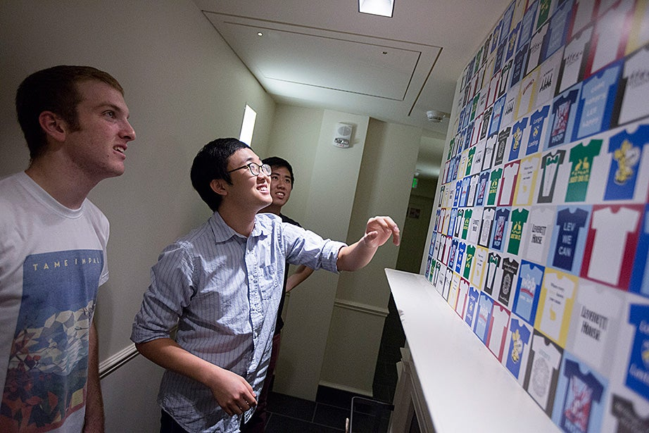Mark Steinbach '17 (from left), Andrew Paek, and Jason Shen '17 look at a collage of House T-shirt designs. Kris Snibbe/Harvard Staff Photographer