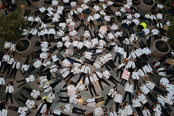 """More than 100 Harvard Medical School students, joined by faculty and staff, took part in a nationwide medical student """"die-in"""" this past Wednesday, lying on the floor of Harvard's Tosteson Medical Education Center on Longwood Avenue in Boston for 15½ minutes (photo 1). Harvard President Drew Faust (photo 2) and Bill Lee (photo 3), the senior fellow of the Harvard Corporation, don T-shirts that read: """"Black Lives Matter."""""""