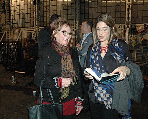"""Author and syndicated columnist Naomi Klein (right) signs a copy of her latest book, """"This Changes Everything: Capitalism vs. the Climate,"""" after a matinee performance of """"O.P.C.,"""" Eve Ensler's new play at the American Repertory Theater."""