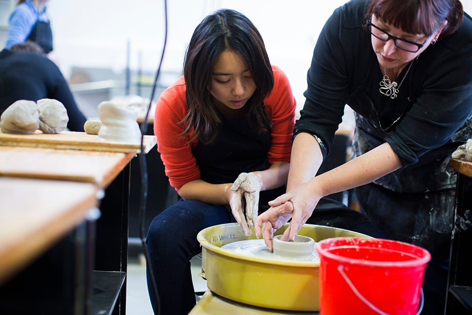 "Students learn basic ceramic-throwing techniques in ""Handmade Mugs."" Karine Hsu '17 (left) works on the wheel under the instruction of Kathy King. Stephanie Mitchell/Harvard Staff Photographer"