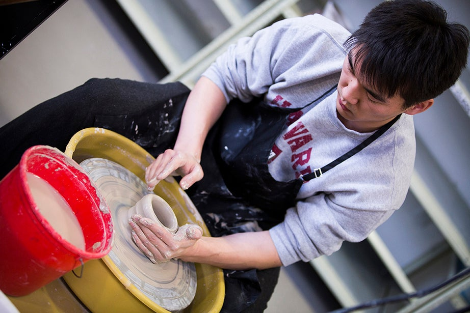 Learning basic ceramic-wheel skills, students wedge, center, and form basic shapes. Perry Choi '15 (pictured) works on the wheel. Stephanie Mitchell/Harvard Staff Photographer