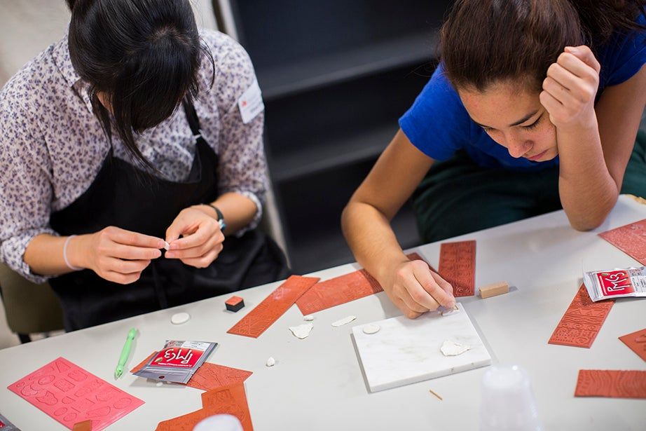 Eliza Chang '16 (left) and Cristina Parajon '18 work with stamps to make jewelry. Stephanie Mitchell/Harvard Staff Photographer