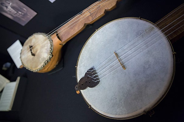 Replicas of a minstrel banjo (foreground, photo 1) and a banza, an African stringed precursor to the banjo, are on view at the Loeb Music Library exhibition. An 1853 map (detail, photo 2) was borrowed from Harvard's Map Collection for the show. Students used the map to help illustrate minstrelsy's wide reach. Samuel Parler (photo 3), a Ph.D. candidate in music, and the chair of Harvard's Music Department Carol Oja conceived of the minstrelsy seminar and resulting exhibition.