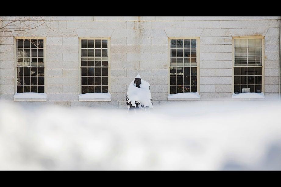 Harvard University on a winter day. Snow covers the John Harvard Statue in Harvard Yard, where it's piled high. Stephanie Mitchell/Harvard Staff Photographer