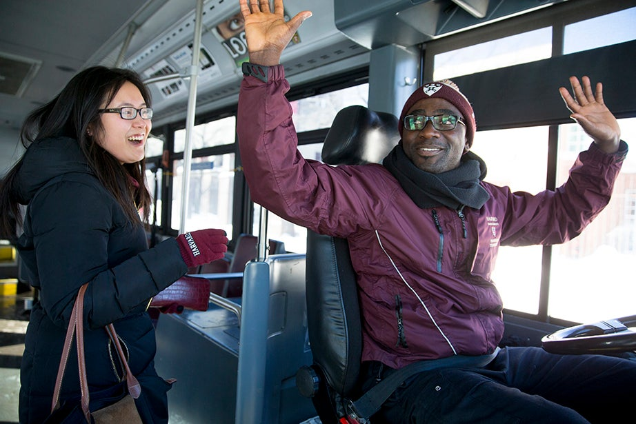 Harvard bus driver Raymond Quitumba Jr. jokes with Yan Bai '15 that she should wave her arms instead of chasing the bus. Rose Lincoln/Harvard Staff Photographer