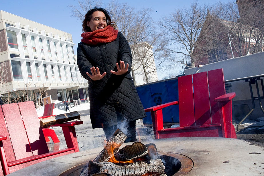Harvard University student Gigi Estevez warms her hands by one of three new fire pits in Science Center Plaza. Rose Lincoln/Harvard Staff Photographer